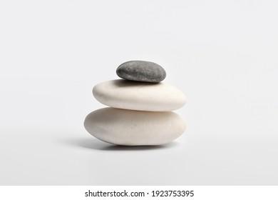 Pyramid of three Zen stones on a white background.