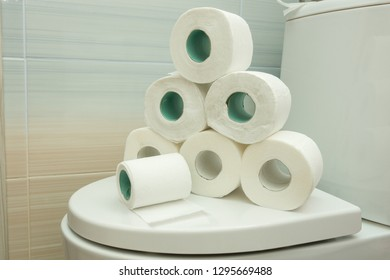 The pyramid of toilet rolls lies on the lid of the toilet bowl