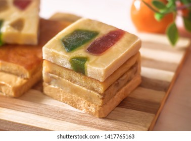 The pyramid of the turron with marmalade on a wooden tray. Selective focus. Blurred background. Traditional Spanish Christmas candy. Marzipan, almonds.