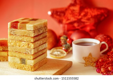 The pyramid of the turron with marmalade on a wooden tray, a red background with Christmas decorations. Cup of coffee. Selective focus. Blurred background. Spanish Christmas candy. Slices of lemon.