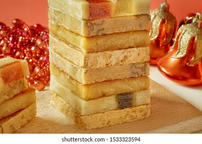 The pyramid of the turron with marmalade on a wooden tray, a red background with Christmas decorations. Selective focus. Blurred background. Traditional Spanish Christmas candy. Texture, layers.