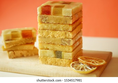 The pyramid of the turron with marmalade on a wooden tray. Selective focus. Blurred background. Spanish Christmas candy. Marzipan, almonds.