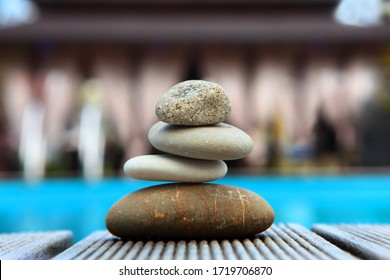 Pyramid of various sea pebbles on the edge of the pool and against the background of gazebos for relaxation. The concept of life balance and harmony. A copy of this place.