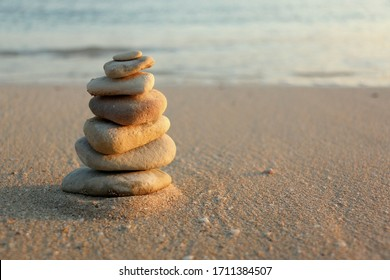 Pyramid of Zen Stones on Sandy Beach with Ocean Water Background. Beautiful Seascape Rest Holiday Concept. Peace Harmony Balance Meditation Yoga Vitality Positive Energy and Thinking Spa Banner Image.