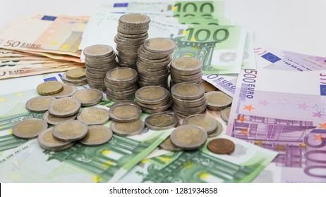 pyramidal pile of euro coins over euro banknotes