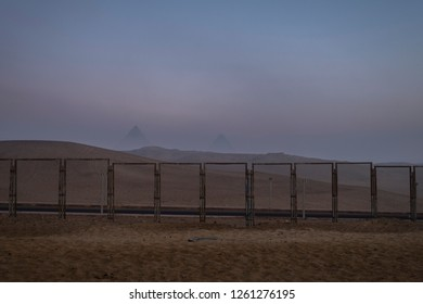Pyramids of egypt covered by camera observated fence in the desert at a foggy morning