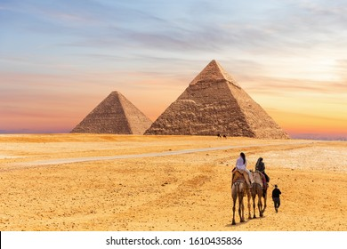 Pyramids of Giza and the tourists on a camel, Egypt
