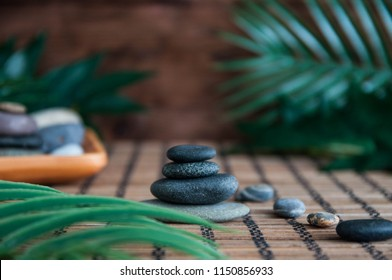 Pyramids of gray zen stones with beautiful fresh white flowers and Buddha statue. Concept of harmony, balance and meditation, spa, massage, relax
