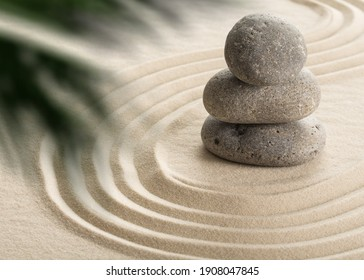 Pyramids of gray zen stones on the white sand with abstract wave drawings. Concept of harmony, balance and meditation, spa, massage, relax.