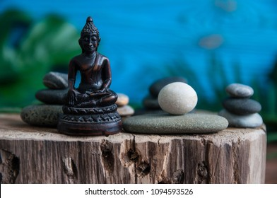 Pyramids of gray zen stones with small wooden Buddha statue. Concept of harmony, balance and meditation, spa, massage, relax