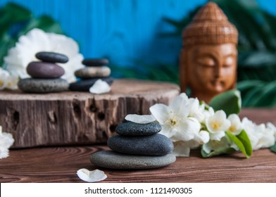 Pyramids of gray zen stones with statue of Buddha and fresh white flowers. Concept of harmony, balance and meditation, spa, massage, relax