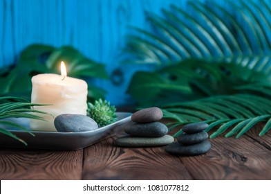 Pyramids of gray zen stones with white candle. Concept of harmony, balance and meditation, spa, massage, relax