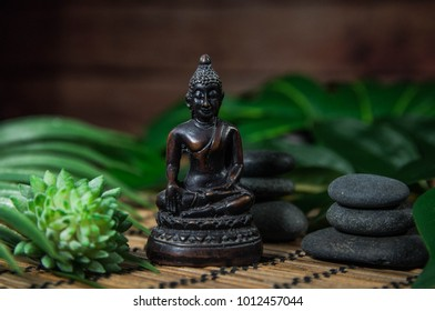 Pyramids of gray zen stones and wooden Buddha. Concept of harmony, balance and meditation, spa, massage, relax