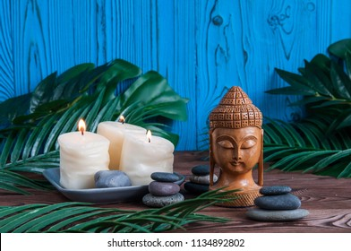Pyramids of gray zen stones with wooden Buddha statue and white candles. Concept of harmony, balance and meditation, spa, massage, relax