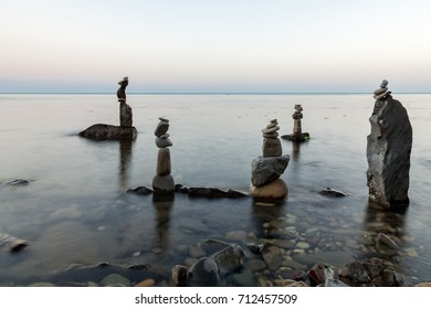 Pyramids of stones in the sea after sunset. The background is blurred.