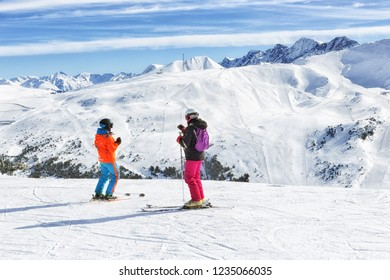 PYRENEES, ANDORRA - FEBRUARY 9, 2018: Skiers stand and look at the slopes at the top of the mountain, at the beginning of the descent. Sunny winter day in the Pyrenees, Andorra