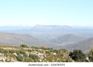 The Pyrenees mountains and ranges covered with snow as seen from the Mallos de Riglos pre-Pyrenees peaks during a sunny winter day in Aragon, Spain