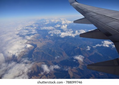 Pyrenees as seen from plane. Aerial view of the high mountains. Mountain range seeing from above. Clouds and Earth scenery. Wing of the plane and beautiful scape during flight.