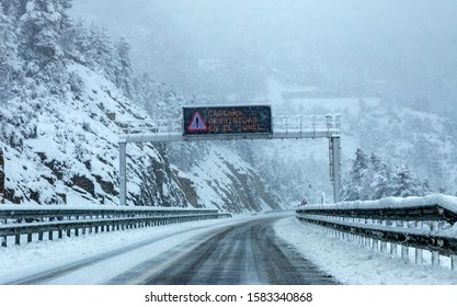 Pyrenees, Spain - Circa december 2018: Heavy snow storm in a road in the Pyrenees region, north of Spain. Road sign alerting of the need of snow chains in you vehicle and closed tunnel