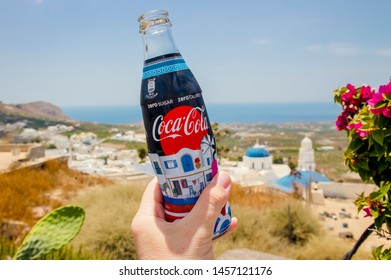 Pyrgos, Santorini /Greece-15JUL2019. Hand holding custom made Coca Cola zero bottle with special Santorini island theme picture on the label. Rare collectable item.
