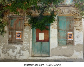 """PYRGOS, TINOS / GREECE - JULI 26 2016: Old stone house with wooden door and windows, where festival's music events are promoted, """"Giorgos Dalaras""""."""