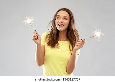 pyrotechnics and people concept - smiling young woman or teenage girl in blank yellow t-shirt with two sparklers over grey background