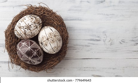 Pysanky in the nest on white wooden background. Easter eggs decorated with wax-resist dyeing technique, traditional for Eastern European countries, wide format, top view, copy space