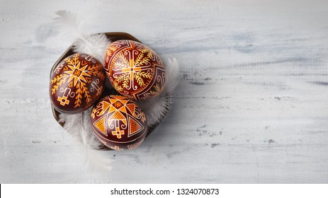 Pysanky on a small plate, Ukrainian Easter eggs decorated with wax-resist dyeing technique, white feathers, wooden background, copy space for text