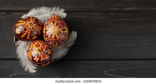 Pysanky on a small plate, Ukrainian Easter eggs decorated with wax-resist dyeing technique, white feathers, black wooden background, copy space for text