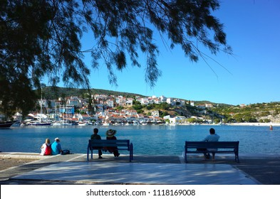 Pythagorion, Samos island, Greece - 13 May, 2018: People sit on benches with view with Pythagorio village on hill over blue water bay