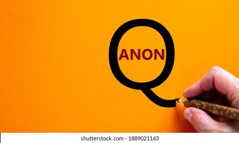 Q Anon symbol. Hand writing words 'Q Anon', isolated on beautiful orange background. Business and q Anon concept, copy space.