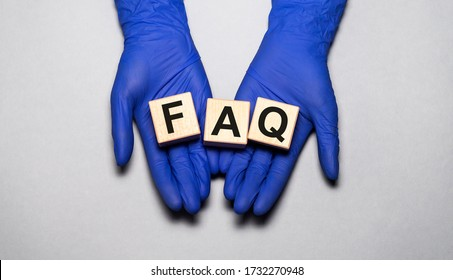 Q & A FAQ Questions and answers on wooden cube blocks in female hands in dark blue gloves over grey blue table