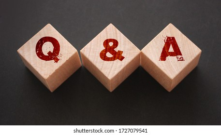 Q and A on wooden blocks Close-up Shot . Question and answers support center business concept.