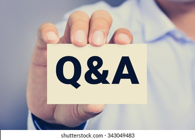 Q & A (Questions and Answers) sign on business card shown by a man, vintage tone