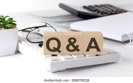 Q and A written on a wooden cube on the keyboard with office tools