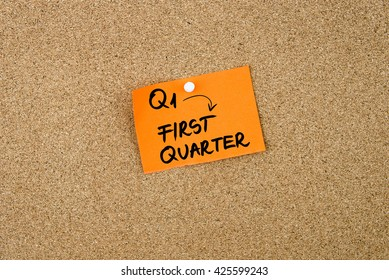 Q1 as FIRST QUARTER written on orange paper note pinned on cork board with white thumbtacks, copy space available