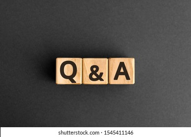 Q&A - acronym from wooden blocks with letters, questions and answers Q&A concept,  top view on grey background