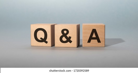 Q&A - acronym from wooden blocks with letters, questions and answers Q&A concept on grey background
