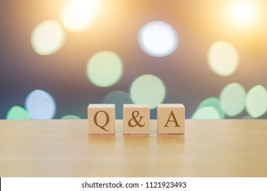 QA questions answers on 3 wooden cubes on a beautiful bokeh blurred background with lights
