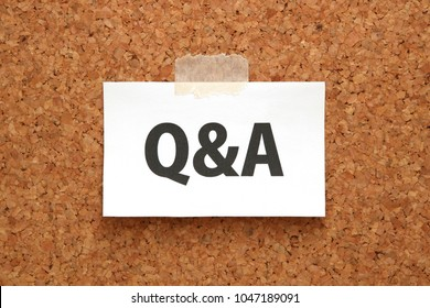 Q&A or Questions and Answers on a piece of white paper on a brown cork board. Q&A or Questions and Answers concept.