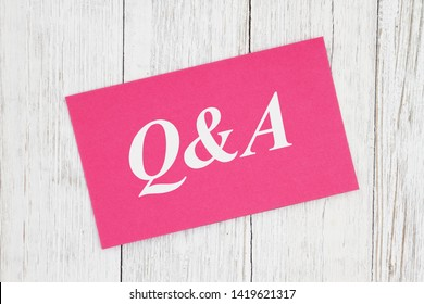 Q&A text on pink card on weathered whitewash textured wood