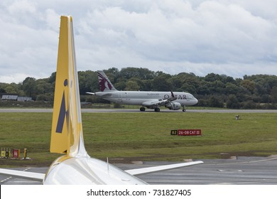 Qatar Airways Airbus A320 aircraft, A7-LAH, with a Monarch Airlines tail in the foreground, having just arrived from Mahon on October 7th 2017 at London Luton Airport, Bedfordshire, UK