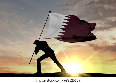 Qatar flag being pushed into the ground by a male silhouette. 3D Rendering