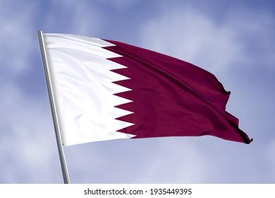 Qatar flag isolated on sky background. close up waving flag of Qatar. flag symbols of Qatar.