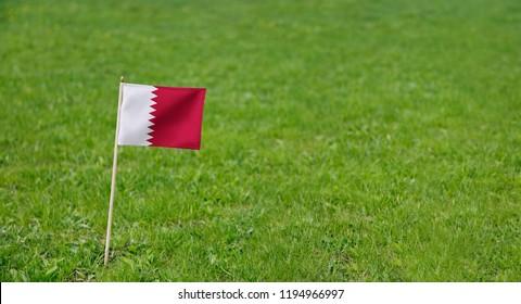 Qatar Flag. Photo of Qatar flag on a green grass lawn background. National flag waving outdoors.