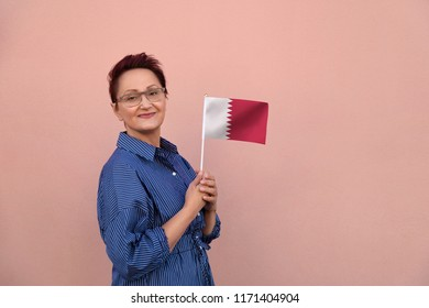 Qatar flag. Woman holding Qatar flag. Nice portrait of middle aged lady 40 50 years old with a national flag over pink wall background outdoors.