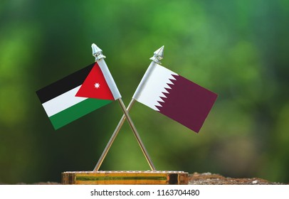 Qatar and Jordan small flag with blur green background