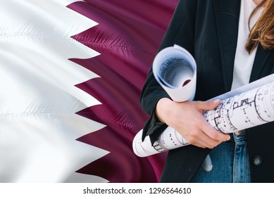 Qatari Architect woman holding blueprint against Qatar waving flag background. Construction and architecture concept.