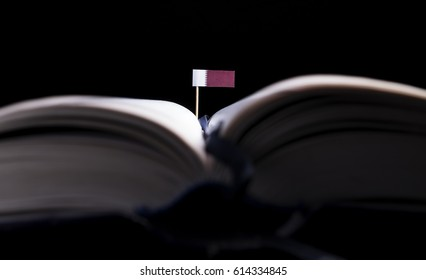 Qatari flag in the middle of the book. Knowledge and education concept.