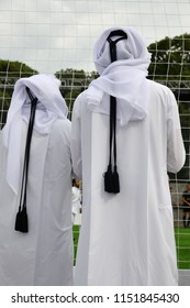 Qatari men in traditional clothes watch the game on a football stadium